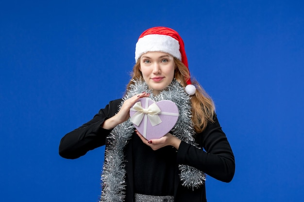 Vorderansicht der jungen frau mit neujahrsgeschenk an blauer wand