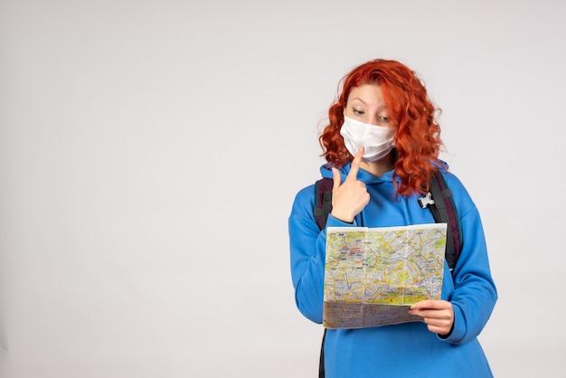 Vorderansicht der jungen frau mit rucksack und karte in der maske auf weißer wand