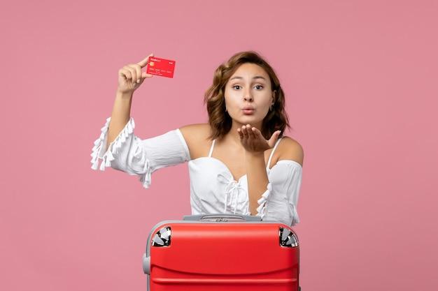 Vorderansicht der jungen frau mit urlaubstasche mit bankkarte an hellrosa wand