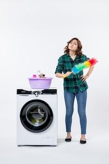 Vorderansicht der jungen frau mit waschmaschine an der weißen wand