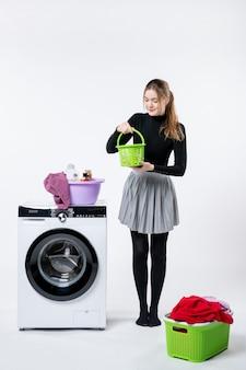 Vorderansicht der jungen frau mit waschmaschine und schmutziger kleidung auf weißer wand