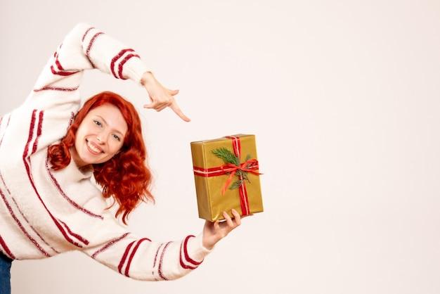 Vorderansicht der jungen frau mit weihnachtsgeschenk auf weißer wand