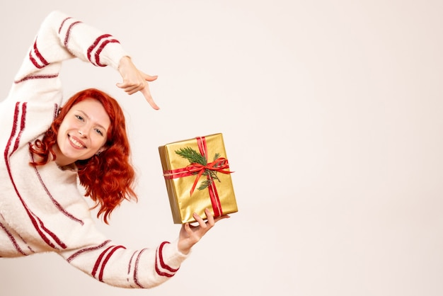 Vorderansicht der jungen frau mit weihnachtsgeschenk lächelnd auf weißer wand