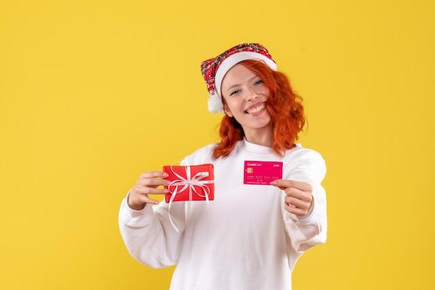 Vorderansicht der jungen frau mit weihnachtsgeschenk und bankkarte auf gelber wand