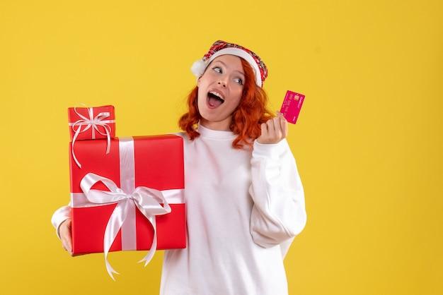 Vorderansicht der jungen frau mit weihnachtsgeschenken und bankkarte auf gelber wand