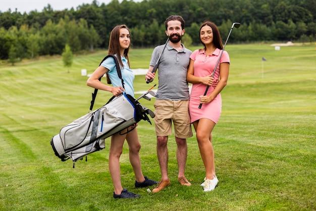 Vorderansicht der jungen golfspieler, die kamera betrachten