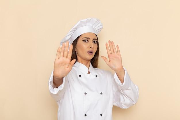 Vorderansicht der jungen köchin im weißen kochanzug, der auf hellweißer wand aufwirft