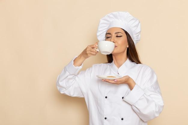 Vorderansicht der jungen köchin im weißen kochanzug, der kaffee auf weißer wand trinkt