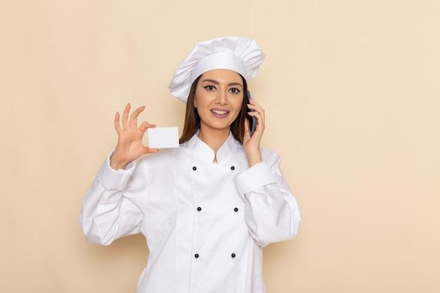Vorderansicht der jungen köchin im weißen kochanzug, der karte hält und am telefon auf hellweißer wand spricht