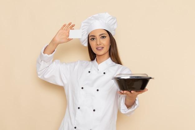 Vorderansicht der jungen köchin im weißen kochanzug, der karte und schüssel auf weißer wand hält
