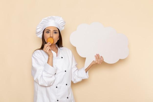 Vorderansicht der jungen köchin im weißen kochanzug, der keks und weißes zeichen auf weißer wand hält