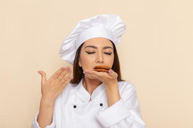 Vorderansicht der jungen köchin im weißen kochanzug, der kekse auf hellweißer wand hält