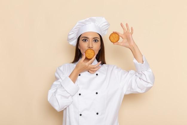 Vorderansicht der jungen köchin im weißen kochanzug, der kleine kekse an der hellweißen wand hält