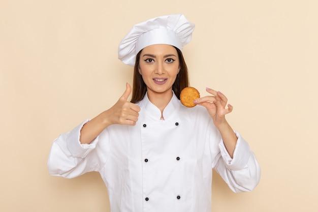 Vorderansicht der jungen köchin im weißen kochanzug, der kleinen keks auf hellweißer wand hält
