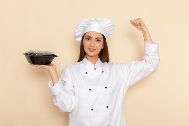Vorderansicht der jungen köchin im weißen kochanzug, der pfanne hält und auf weißer wand biegt