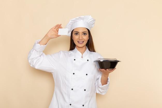 Vorderansicht der jungen köchin im weißen kochanzug, der schwarze schüssel und karte auf heller weißer wand hält