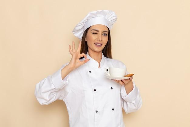 Vorderansicht der jungen köchin im weißen kochanzug, der tasse kaffee hält und auf weißer wand zwinkert
