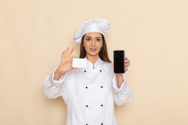 Vorderansicht der jungen köchin im weißen kochanzug, der telefon und karte auf hellweißer wand hält