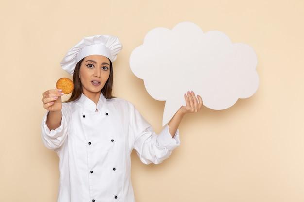 Vorderansicht der jungen köchin im weißen kochanzug, der weißes zeichen auf hellweißer wand hält