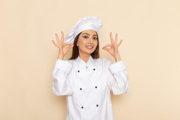 Vorderansicht der jungen köchin im weißen kochanzug lächelnd auf hellweißer wand