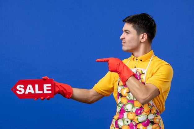 Vorderansicht der jungen männlichen haushälterin in gelbem t-pullover, die ein verkaufsschild hält, das nach links an der blauen wand zeigt