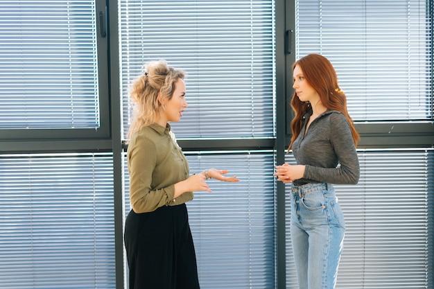 Vorderansicht der jungen rothaarigen geschäftsfrau, die ein geschäftsgespräch mit einem kaukasischen mitarbeiter führt, besprechen sie projektarbeit im büroraum durch fenster. junge geschäftsfrau, die kollegen vor dem treffen grüßt.