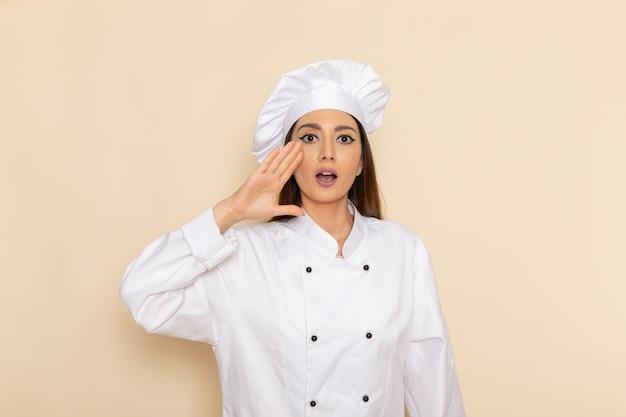 Vorderansicht der jungen weiblichen köchin im weißen kochanzug, der auf weißer wand aufwirft