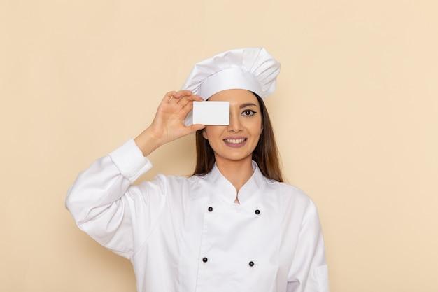 Vorderansicht der jungen weiblichen köchin im weißen kochanzug, der karte mit lächeln auf hellweißer wand hält