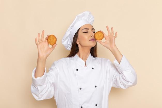 Vorderansicht der jungen weiblichen köchin im weißen kochanzug, der kekse auf weißer wand hält