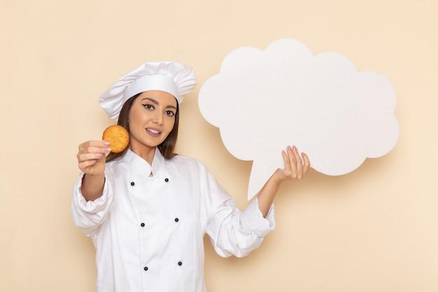 Vorderansicht der jungen weiblichen köchin im weißen kochanzug, der kekse und weißes zeichen auf hellweißer wand hält