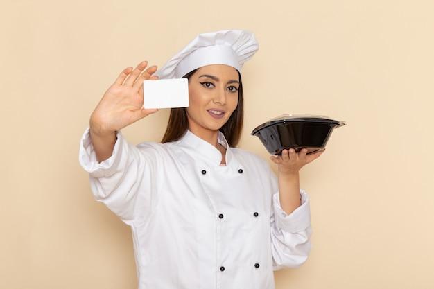 Vorderansicht der jungen weiblichen köchin im weißen kochanzug, der pfanne und karte auf weißer wand hält