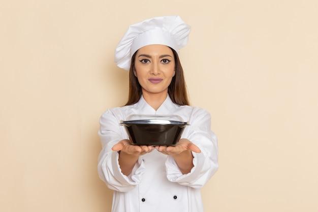 Vorderansicht der jungen weiblichen köchin im weißen kochanzug, der schwarze schüssel auf weißer wand hält