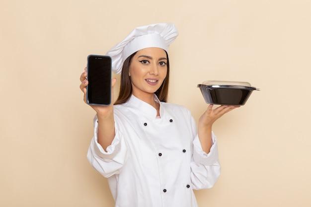 Vorderansicht der jungen weiblichen köchin im weißen kochanzug, der telefon und schwarze schüssel auf weißer wand hält