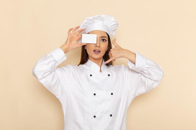 Vorderansicht der jungen weiblichen köchin im weißen kochanzug, der weiße karte auf weißer wand hält