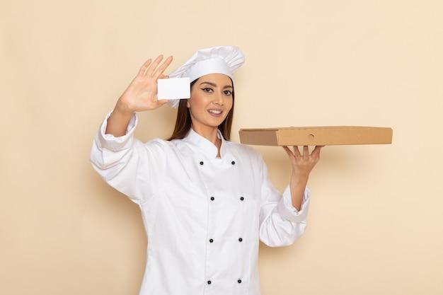 Vorderansicht der jungen weiblichen köchin im weißen kochanzug, der weiße karte und lebensmittelbox auf hellweißer wand hält