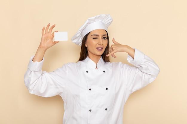 Vorderansicht der jungen weiblichen köchin im weißen kochanzug, der weiße plastikkarte auf weißer wand hält