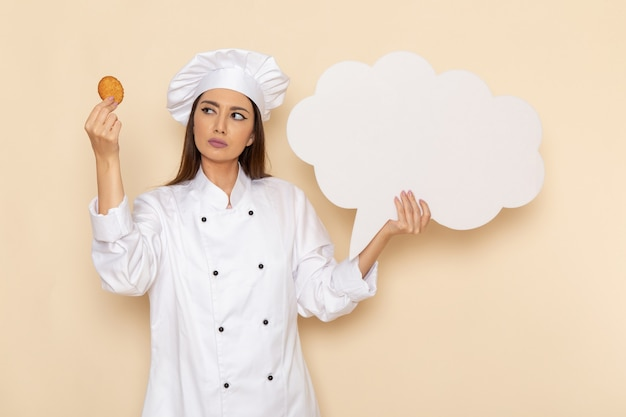 Vorderansicht der jungen weiblichen köchin im weißen kochanzug, der weißes zeichen und keks auf hellweißer wand hält