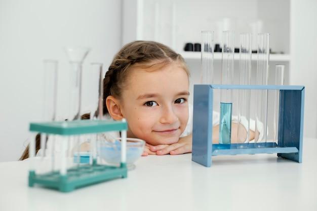 Vorderansicht der jungen wissenschaftlerin mit reagenzgläsern im labor