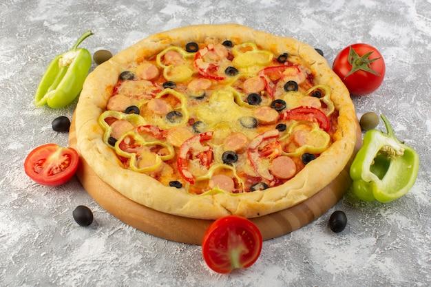 Vorderansicht der käsigen pizza mit oliven, würstchen und roten tomaten auf dem grauen schreibtisch