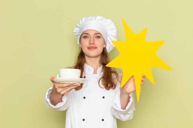 Vorderansicht der köchin im weißen kochanzug, der tasse und gelbes zeichen auf grüner wand hält