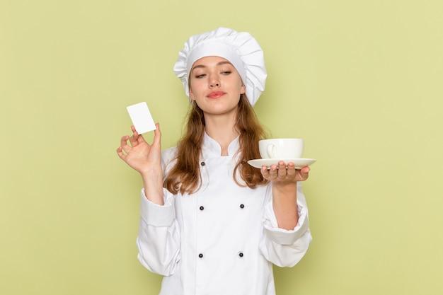 Vorderansicht der köchin im weißen kochanzug, der weiße plastikkarte und tasse auf der grünen wand hält
