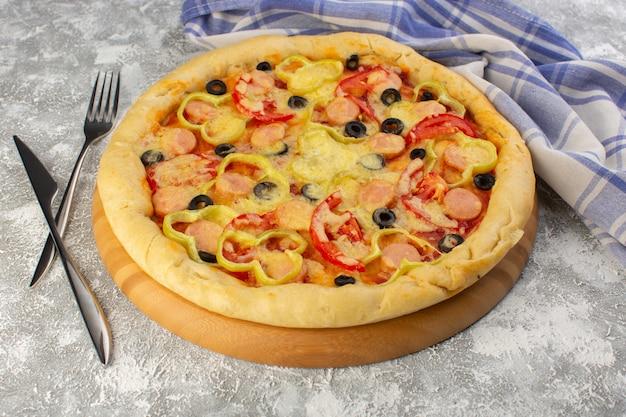 Vorderansicht der köstlichen käsigen pizza mit oliven, würstchen und tomaten