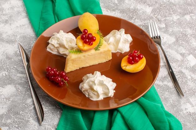 Vorderansicht der köstlichen kuchenscheibe mit aprikosen und sahne innerhalb der braunen platte auf der hellen oberfläche