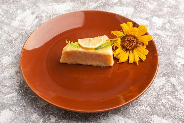 Vorderansicht der köstlichen kuchenscheibe mit zitrone innerhalb der braunen platte mit sonnenblume auf der hellen oberfläche
