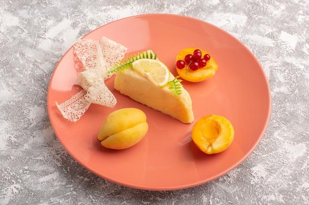 Vorderansicht der köstlichen kuchenscheibe mit zitronenstück und frischen aprikosen auf der hellen oberfläche