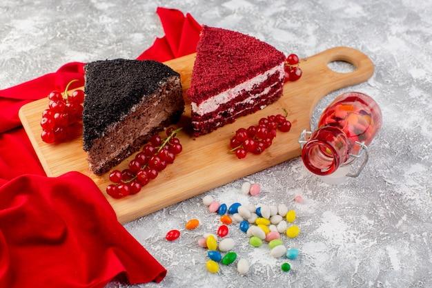 Vorderansicht der köstlichen kuchenscheiben mit sahne-schokolade und früchten auf dem hölzernen schreibtisch