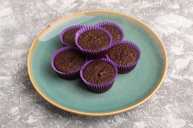 Vorderansicht der köstlichen schokoladenbrownies innerhalb der grünen platte auf der hellen oberfläche