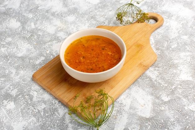 Vorderansicht der köstlichen suppe innerhalb des tellers auf dem graulichtschreibtisch