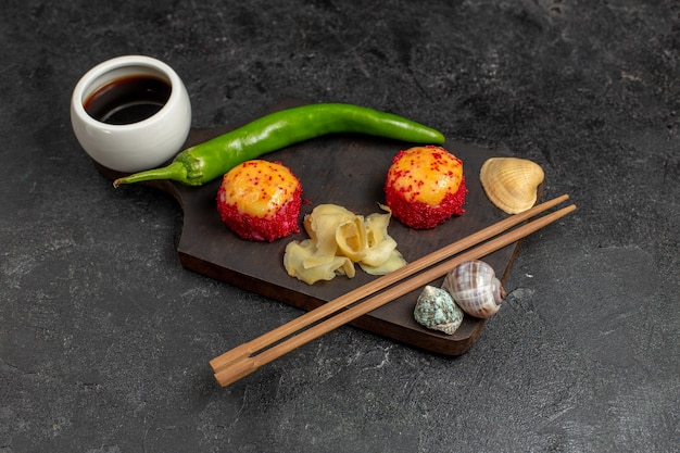 Vorderansicht der köstlichen sushi-fischrollen mit fisch und reis zusammen mit grünem pfeffer und stöcken auf grauer wand