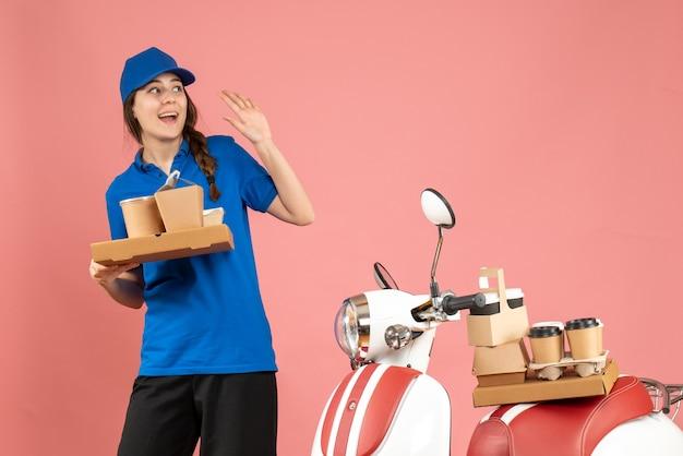 Vorderansicht der kurierdame, die neben dem motorrad steht und kaffee und kleine kuchen auf pastellfarbenem pfirsichhintergrund hält